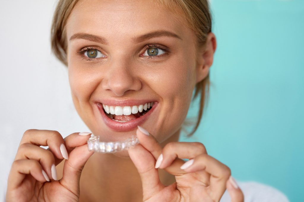 Teeth Whitening. Beautiful Smiling Woman With White Smile, Straight Teeth Using Teeth Whitening Tray. Girl Holding Invisible Braces, Teeth Trainer. Dental Treatment Concept.